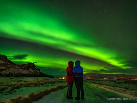 2 people under the norther lights, also known as aurora borealis, in Iceland