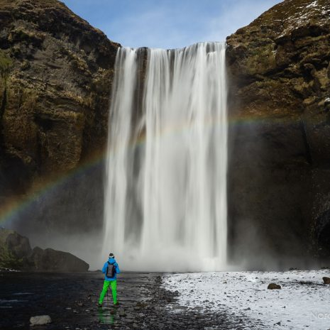 Rainbow and a man before the mighty Skogafoss waterfall on the south coast of Iceland