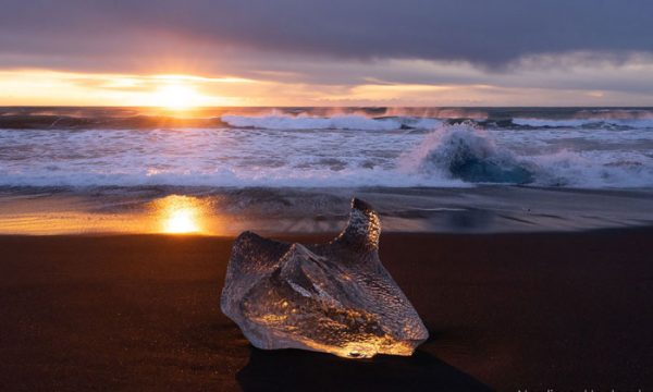An Ice block at sunset on a black sand beach, communly called Diamond beach