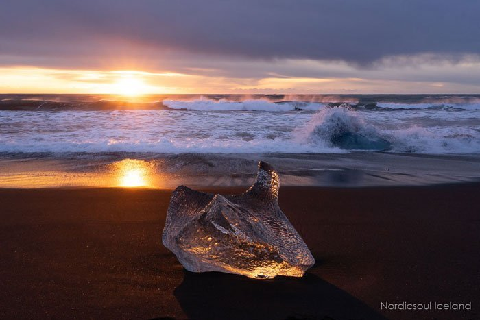 An Ice block at sunset on a black sand beach, communly called Diamond beach