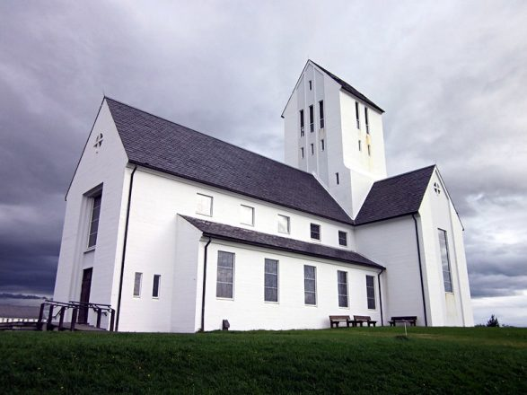 The white church of Skáholt with it's rectangular windows on grey sky background