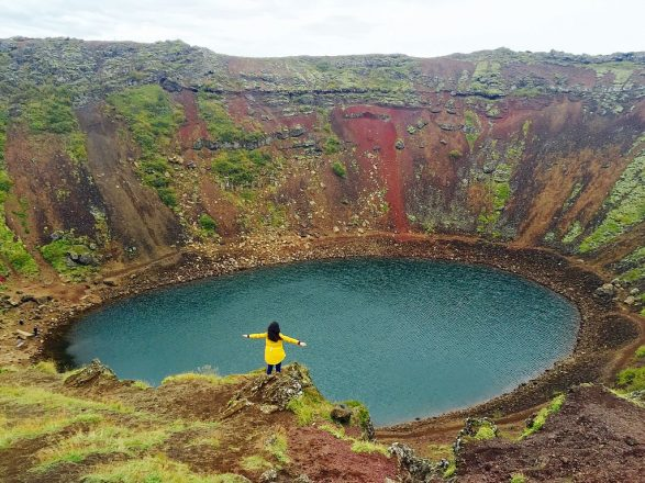 The crater of Kerið, it's aquamarine water and red flanks and a lady with a yellow jacket in front of it.