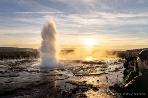Big water eruption at sunset in the valley of Haukadalur where Geysir resides.