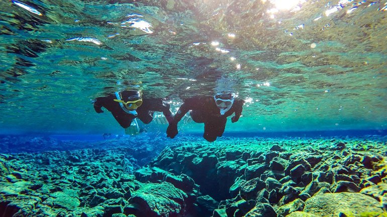 2 snorkelers holding hands in Silfra