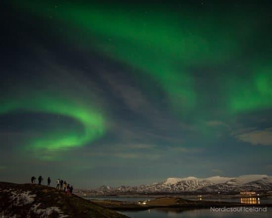 Les aurores boréales dansent dans le ciel du soir.