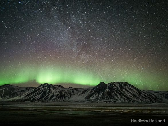 Northern Lights above a mountain and under the stars
