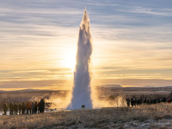 Strokkur Geyser erupting at sunset