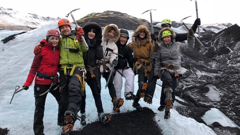 Happy group of people on a glacier hike