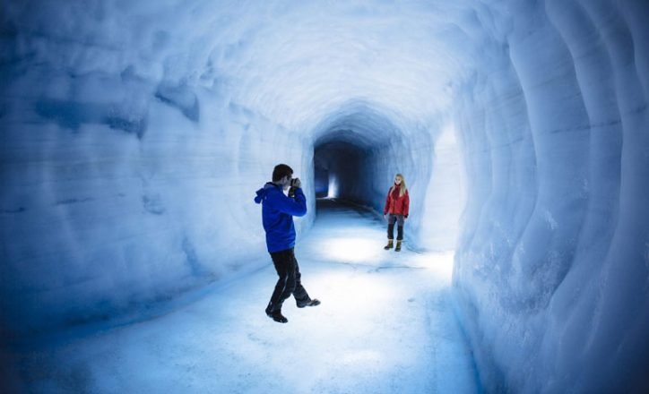 Ice tunnel inside the Langjökull glacier. A person in with a blue Jacket is taking a picture of a person in a red jacket inside the icy tunnel.