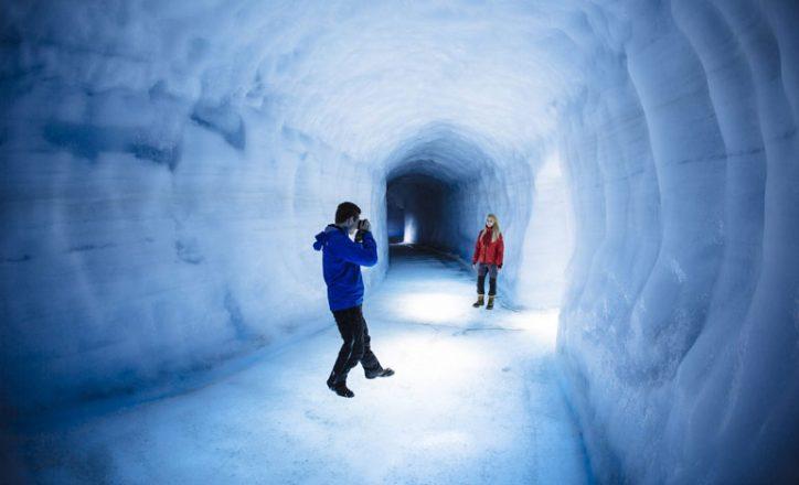 Tunnel de glace à l'intérieur du glacier Langjökull. Une personne avec une veste bleue prend une photo d'une personne dans une veste rouge à l'intérieur du tunnel glacé.