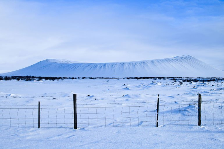Hverfjall volcano crater in the region of Myvatn in northern Iceland covered with snow under a blue sky