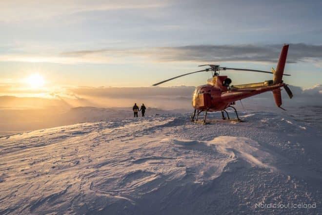 deux personnes se tenant la main au sommet de l'une des montagnes entourant Reykjavik à côté de l'hélicoptère qui les a amenés là-bas