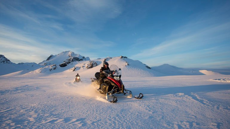 snowmobiles under the sun on Langjokull glacier in Iceland