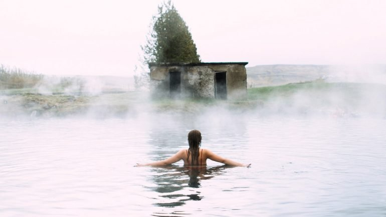 A girl enjoys the waters of the Secret Lagoon