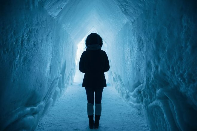 A woman inside Iceland's Ice Cave Tunnels.