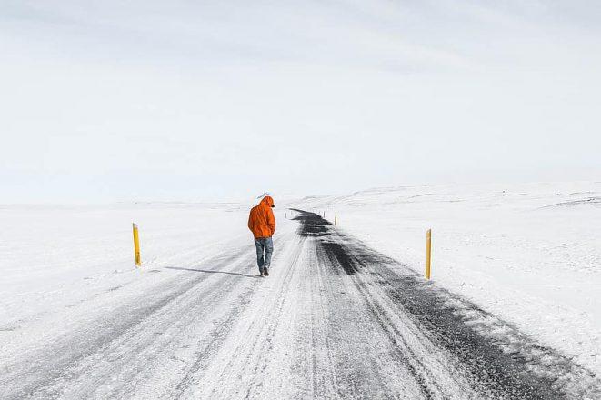 Un homme marchant sur une route glacée en Islande