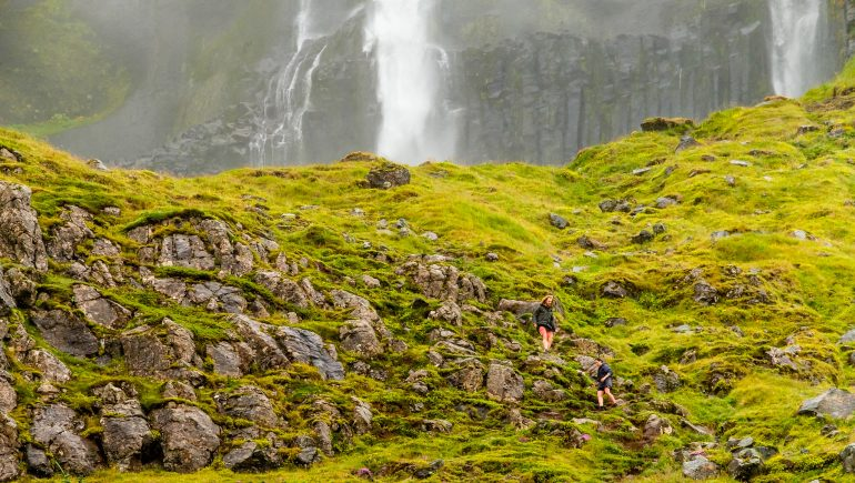 Two people hiking towards Bjarnafoss Waterfall on the Snaefellsnes Peninsula.