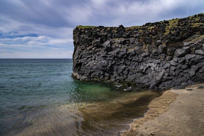 Une falaise menant à l'océan, entourée de sable doré sur la péninsule de Snaefellsnes.