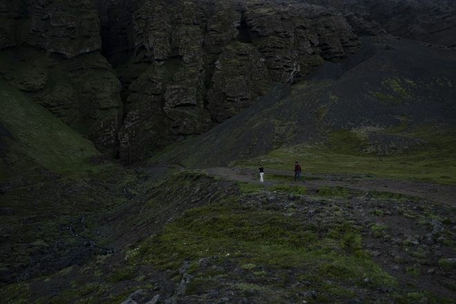 Two people walking towards Raudafeldsgja Gorge on the Snaefellsnes Peninsula.