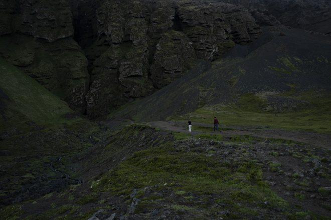 Deux personnes marchant vers la gorge de Raudafeldsgja sur la péninsule de Snaefellsnes.