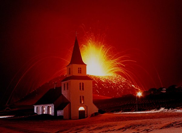 A volcano on the Westman Islands erupting behind a church.