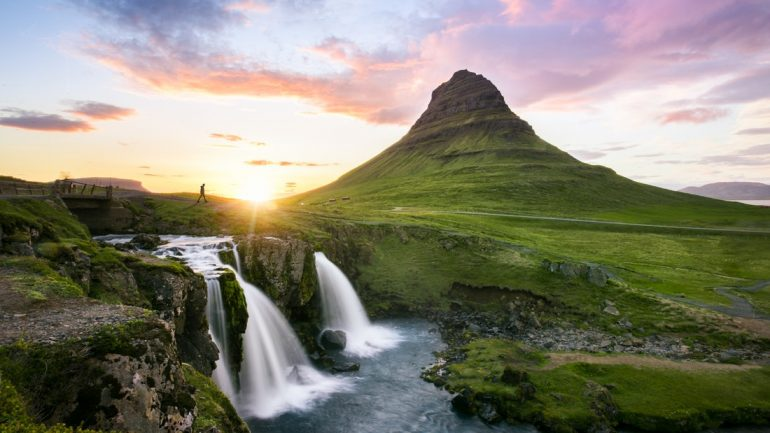 Mt. Kirkjufell and the nearby waterfall, sun shining behind the mountain.