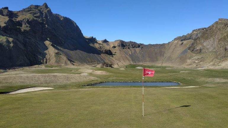 A hole on a golf course surrounded by mountains.