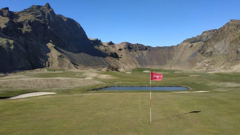 Un trou sur un terrain de golf entouré de montagnes.