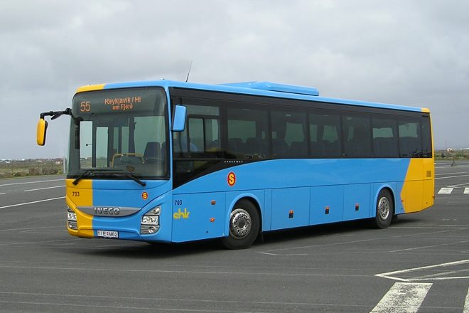 A blue and yellow bus on a parking lot.