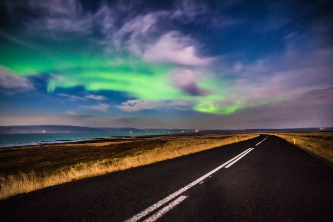 Northern Lights over an empty road in Iceland