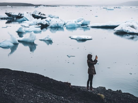 A person taking a photo of Jokulsarlon Glacier Lagoon in Southeast Iceland