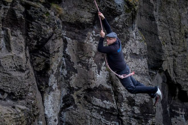 A man holding a rope and swinging from a cliff in the Westman Islands.