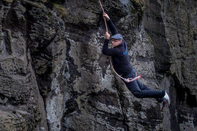 Un homme tenant une corde et se balançant d'une falaise dans les îles Westman.
