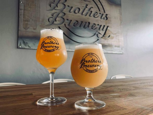 Two glasses of beer in front of a sign saying Brothers Brewery