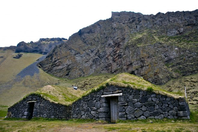 A turf house surrounded by mountains in the Westman Islands