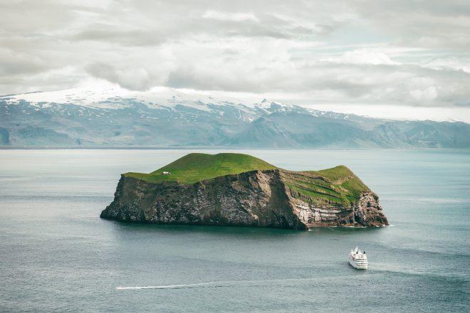 une maison isolée sur l'île Westman avec un ferry qui approche.