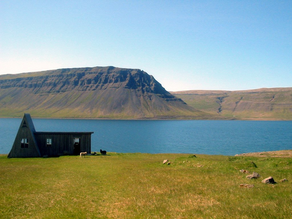 Abandoned house by a fjord and a mountain in the Westfjords of Iceland.