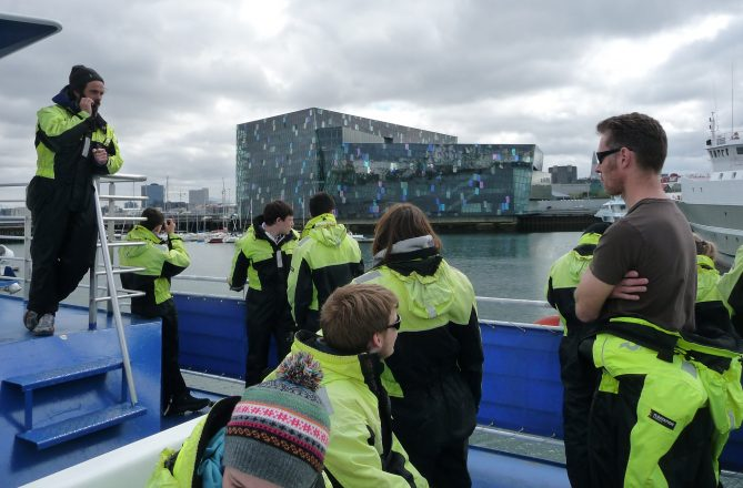 Whale watchers look on Harpa concert hall in Reykjavik.