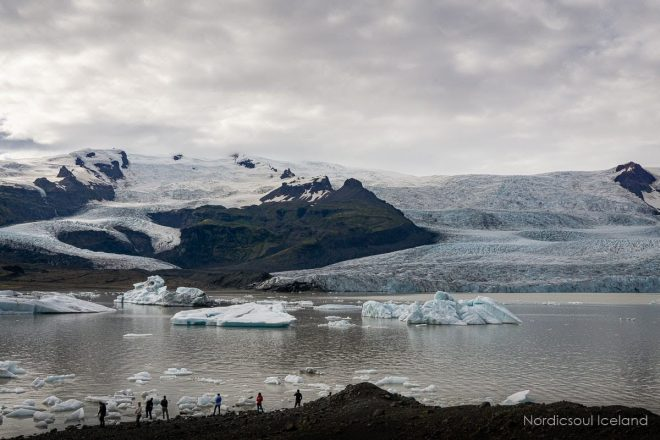 People standing on the shoreline of a glacier lagoon in front of a massive ice cap