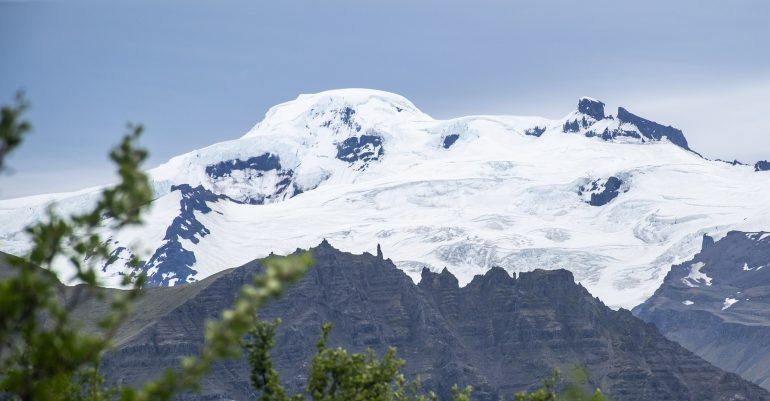 A snow-capped mountain towering over trees at Skaftafell Nature Reserve