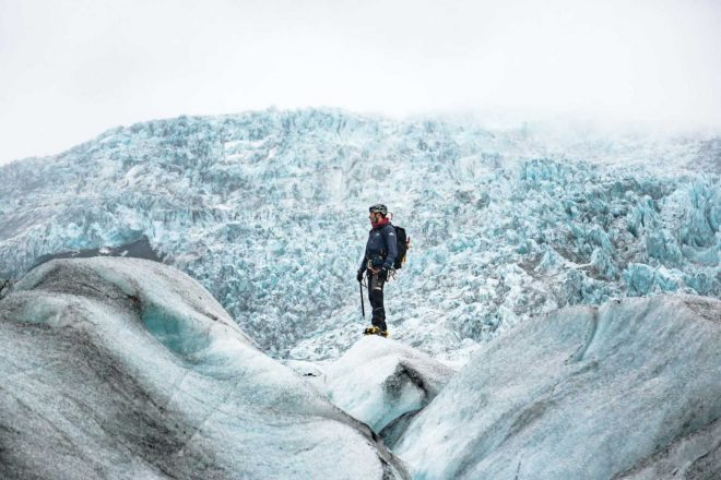 A man in glacier gear standing on a glacier, surrounded by ice