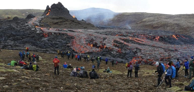 Tourists in front of an erupting volcano in Iceland.