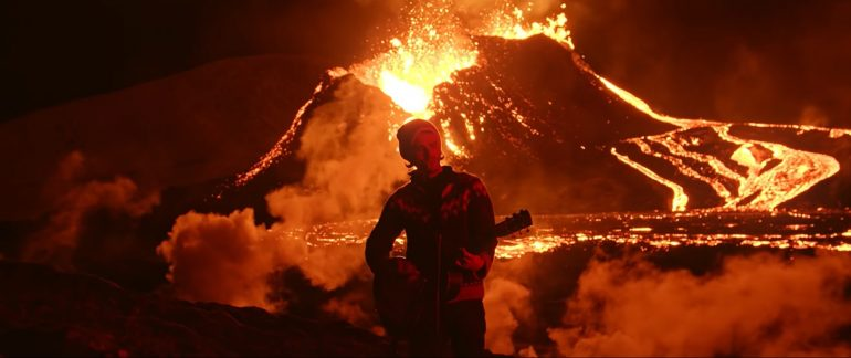 Singer of Icelandic band Kaleo in front of an erupting volcano