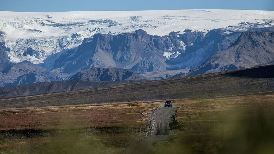 A car driving on a road in the Icelandic Highlands.