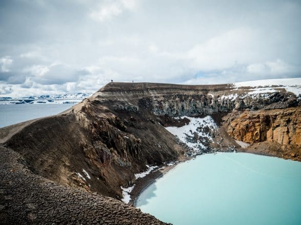 Blue lake and snow-capped mountains in the Icelandic Highlands.