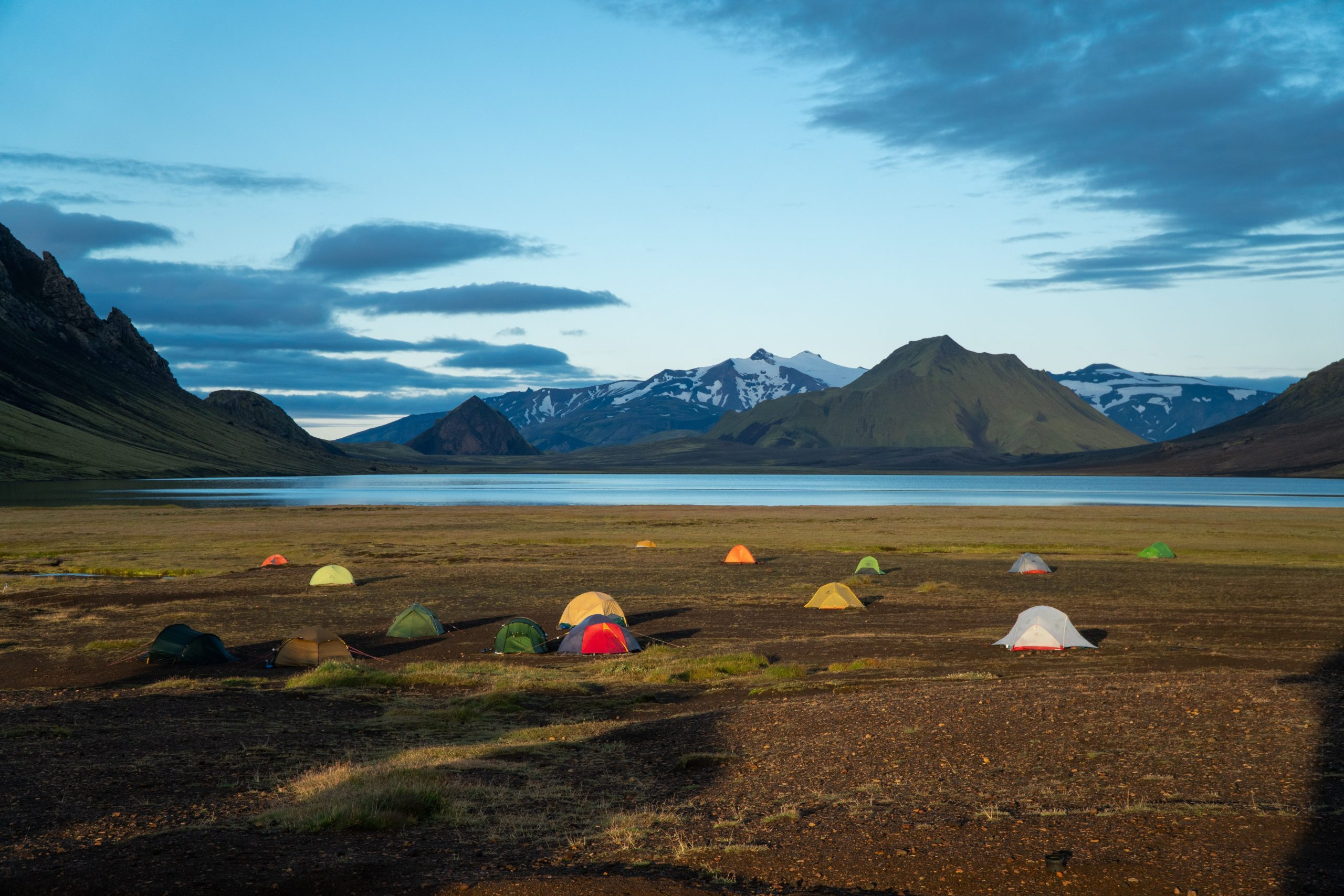 Tents at a campsite in the Icelandic Highlands, overlooking a lake.