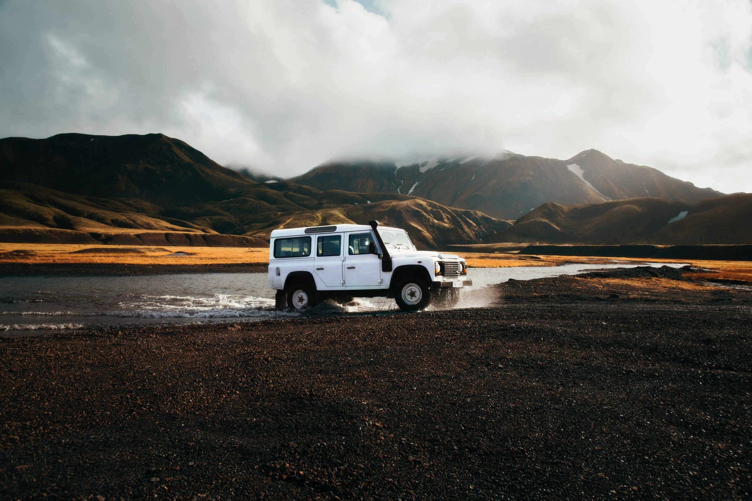 A white car crossing a river in the Icelandic Highlands.