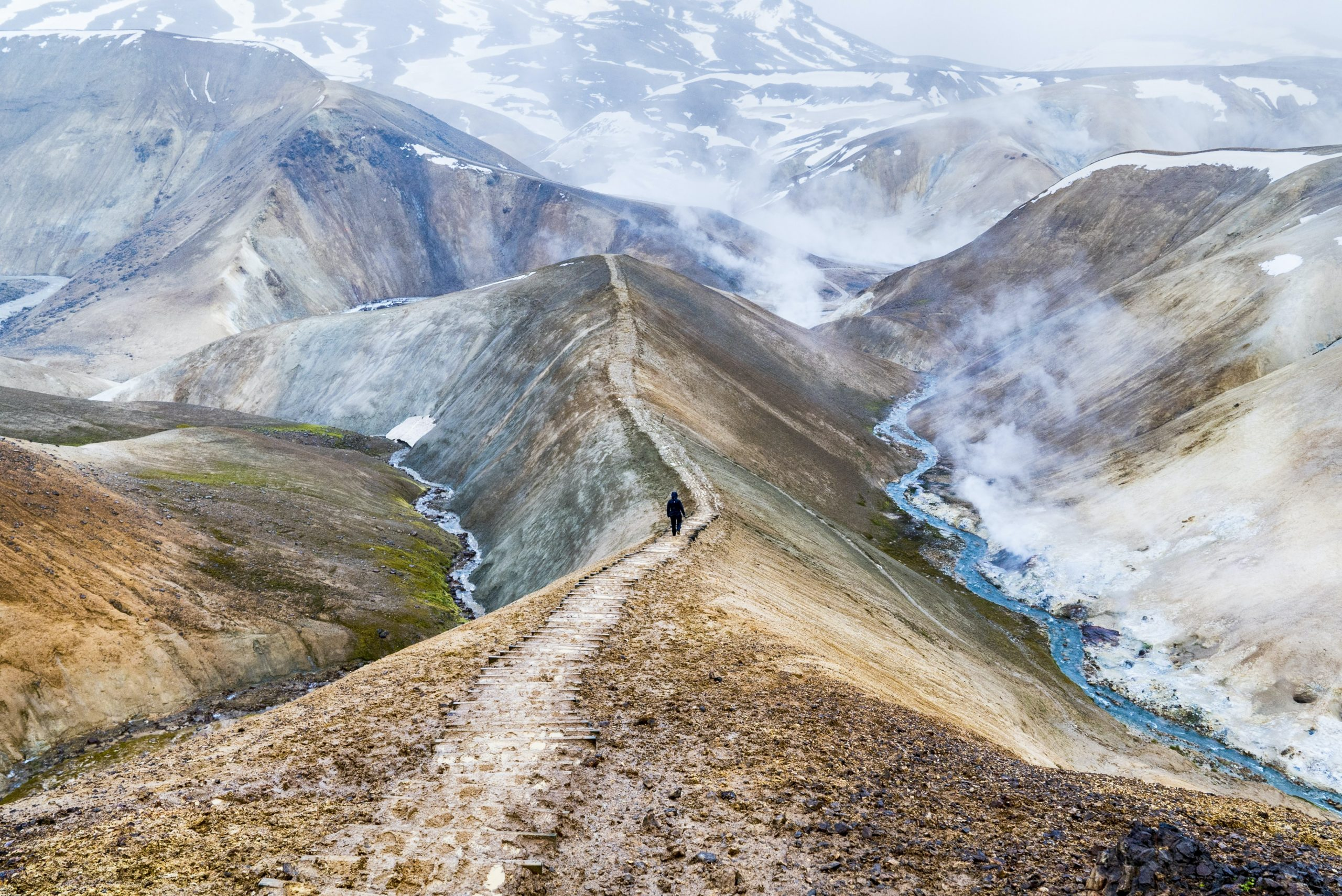 A person walking on a path in Iceland's Highlands, surrounded by steaming mountains.