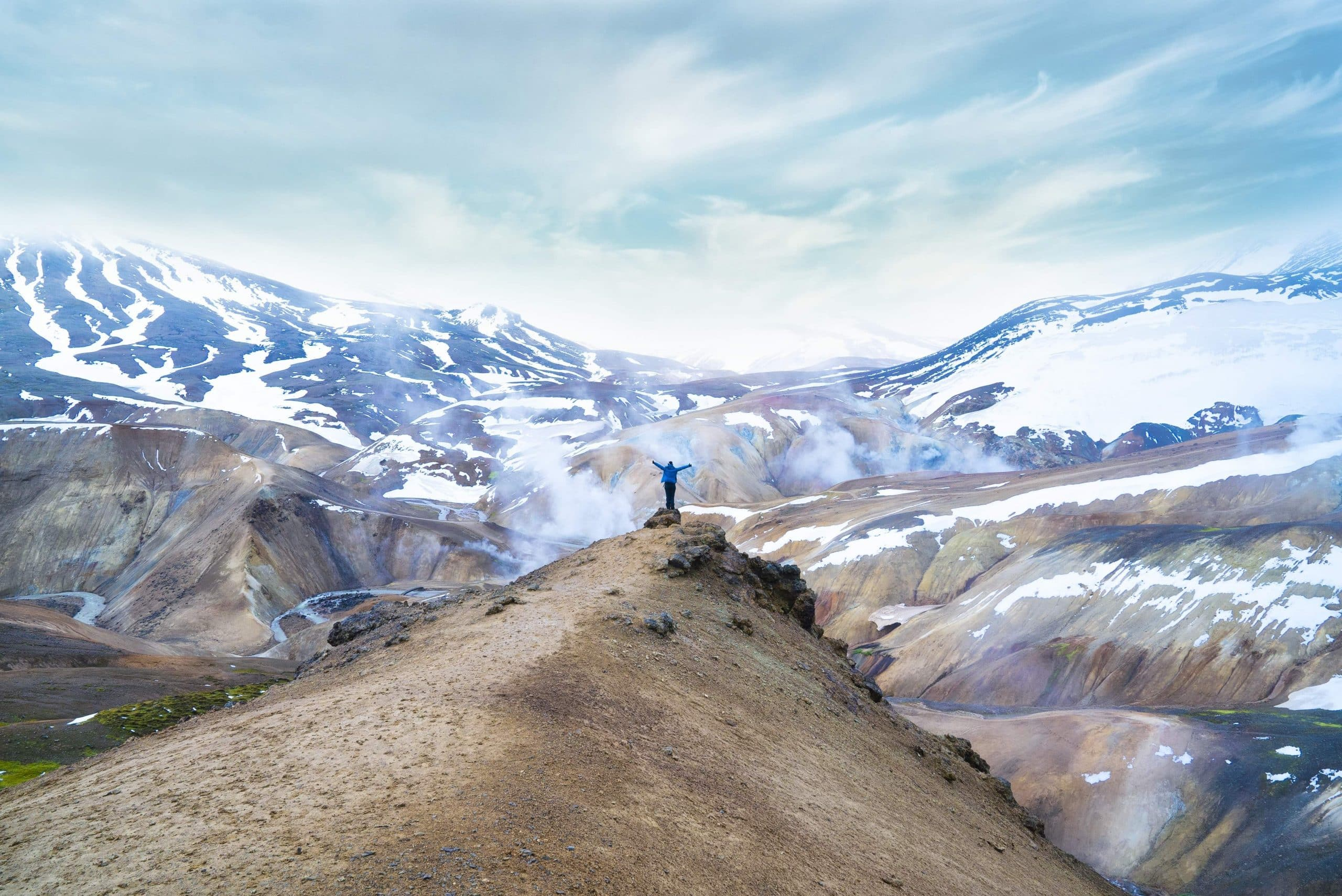 A person standing on a cliff in front of a mountain range in the Icelandic Highlands.