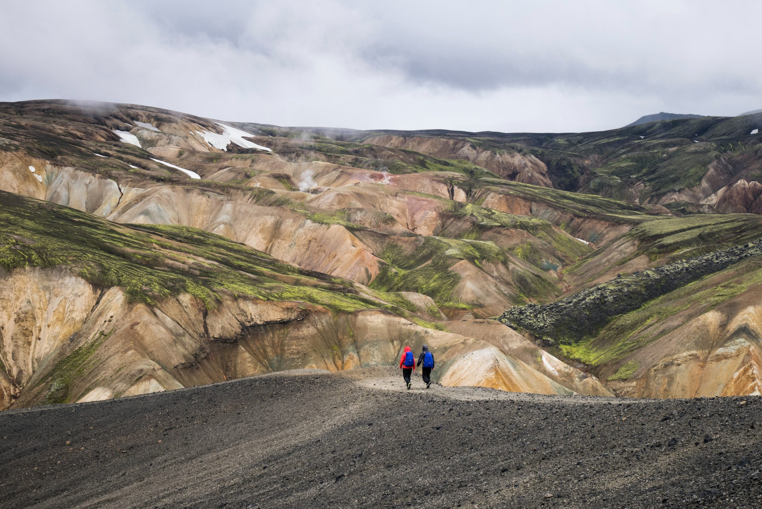 Two people hiking in the Landmannalaugar Region in Iceland's Highlands.